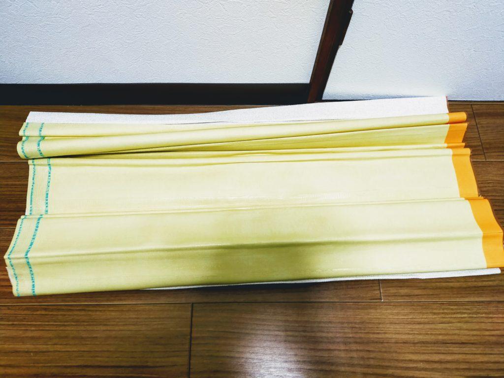壁紙クロス右側カットテープオレンジ。左側下敷きテープ緑